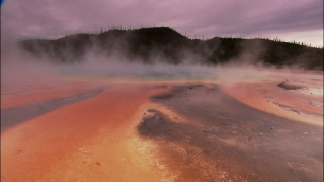 WS Steam rising from thermal pool in barren landscape of red and dark grey soils in Yellowstone National Park / Wyoming, USA