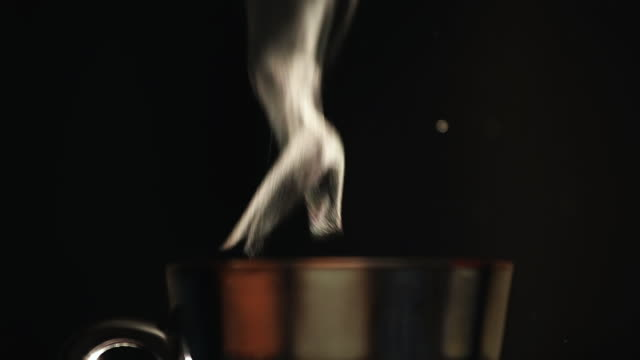 CU of Steam rising off of cup of hot liquid Shot on black back side / Endicott, New York, United States