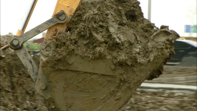 stockvideo's en b-roll-footage met a steam shovel scoops dirt at a construction site in front of hongqiao airport. - handen in een kommetje