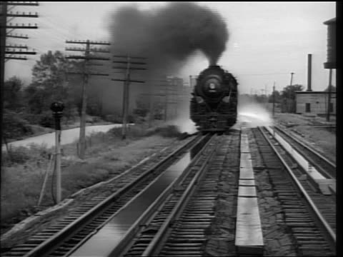 b/w 1937 steam train approaching + passing camera / splashes water on camera - railway track stock videos & royalty-free footage