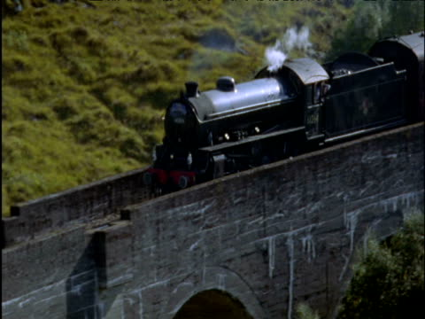 stockvideo's en b-roll-footage met steam train begins to cross curved glenfinnan viaduct scottish highlands - ruimte exploratie