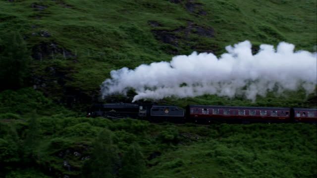 stockvideo's en b-roll-footage met a steam train chugs across the glenfinnan viaduct near argyll, scotland. available in hd. - stoomtrein