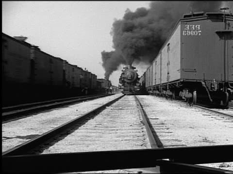 b/w steam train driving on tracks toward + over camera - locomotiva video stock e b–roll