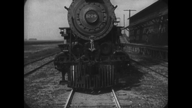 1921 steam train grows ever large until screen is filled with man (buster keaton) sitting on front of train - 無声映画点の映像素材/bロール