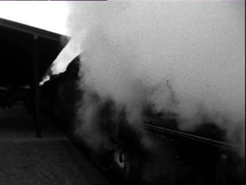 1935 b/w montage steam train leaving station, people waving from train, woman in black fur coat waving white handkerchief after train / braunschweig, lower saxony, germany - railway station stock videos and b-roll footage