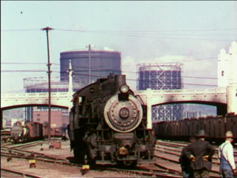 1949 steam train moving slowly on tracks / industrial - 操車場点の映像素材/bロール
