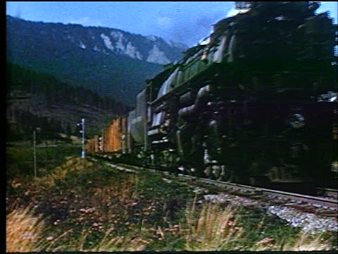 1947 steam train moving slowly towards camera / mountains in background / educational - anno 1947 video stock e b–roll