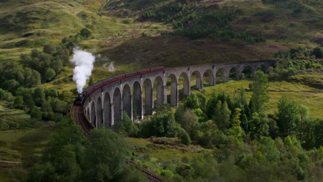 Steam train passes over curved Glenfinnan viaduct. Glenfinnan, Scottish Highlands, Scotland, UK.