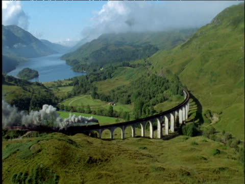 Steam train passes over curved Glenfinnan viaduct Scottish Highlands