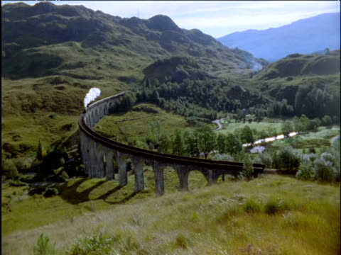 steam train passes over curved glenfinnan viaduct scottish highlands - viaduct stock videos & royalty-free footage