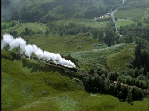 Steam train passes through green countryside Scottish Highlands