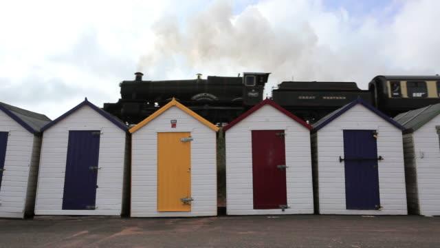 ws la steam train passing beach huts in foreground / goodrington, paignton, devon - locomotive 個影片檔及 b 捲影像