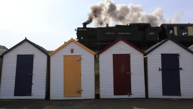 MS LA Steam Train passing beach huts in foreground / Goodrington, Paignton, Devon
