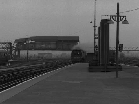 steam train pulling carriages passes through a railway station without stopping. 1956. - 1956 stock-videos und b-roll-filmmaterial