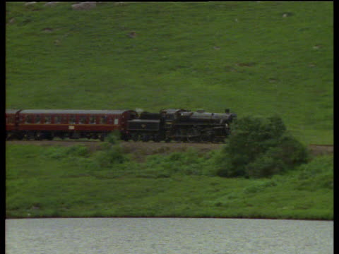 steam train rounds bend in valley camera pans right and zooms out as it travels along side of lake - steam train stock videos & royalty-free footage