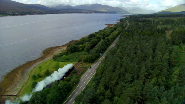 steam train running down towards loch eil  - aerial view - scotland, highland, united kingdom - scottish culture stock videos & royalty-free footage