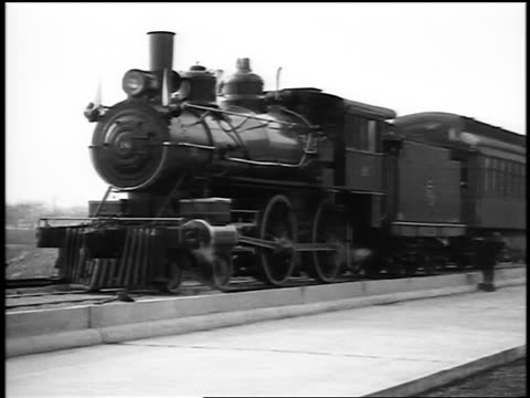 stockvideo's en b-roll-footage met b/w 1915 pan steam train slowly taking off from station / newsreel - 1915