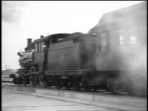 B/W 1915 steam train slowly taking off from station / newsreel
