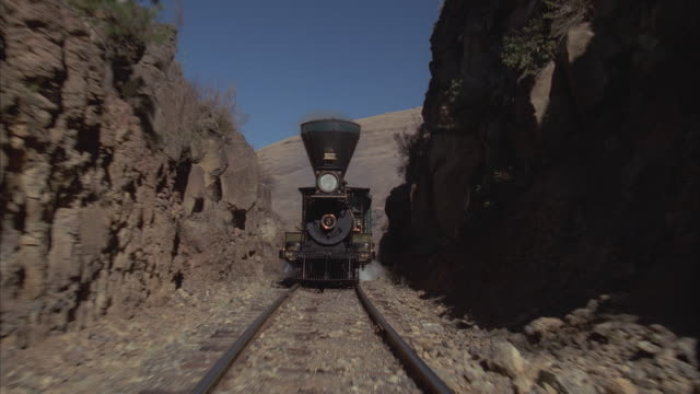WS, POV, REENACTMENT Steam train traveling through rocky landscape, entering tunnel