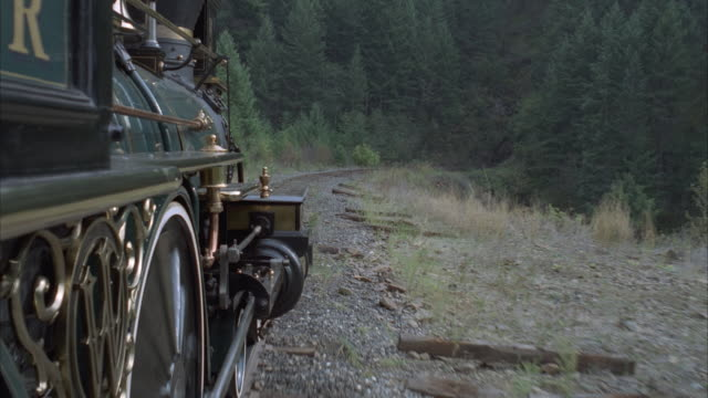 MS, SIDE POV, REENACTMENT Steam train traveling through rocky landscape, entering tunnel