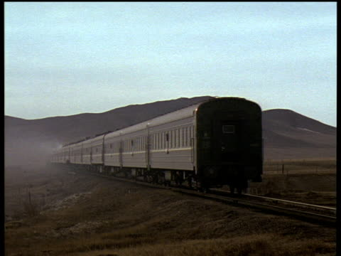 steam train travels along track towards mountains and mist in distance - 1994 stock videos and b-roll footage