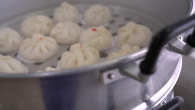 vídeos de stock, filmes e b-roll de cozido no vapor bolinho na panela de vapor. - bolinho de massa