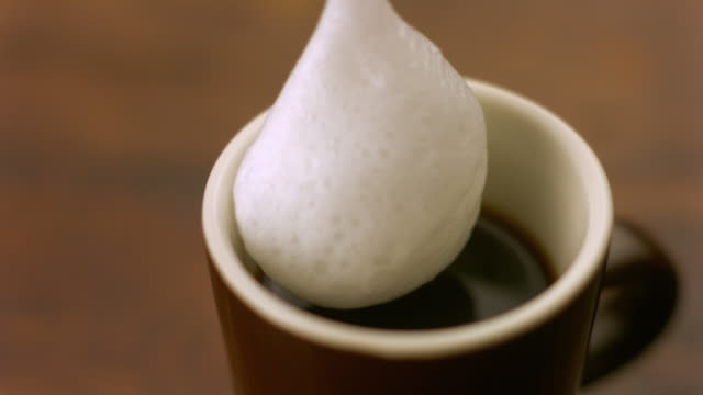 SLO MO CU Steamed milk falling into coffee