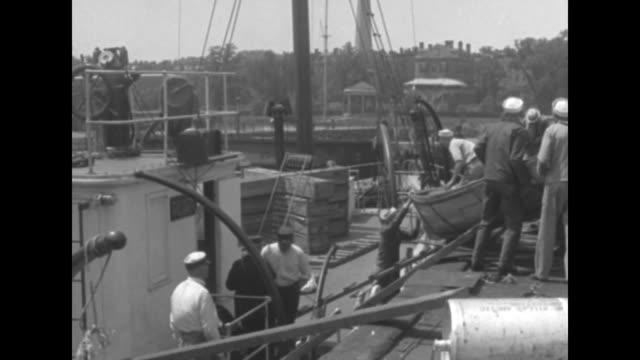 stockvideo's en b-roll-footage met steamer uss peary tied up to dock men on dock and boat / sailors carrying metal boat / sailors lowering boat from dock onto deck / pan sailors... - amfibivoertuig