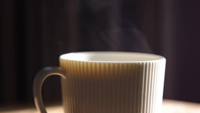 vídeos de stock e filmes b-roll de steaming cup of coffee or tea on table - bebida quente