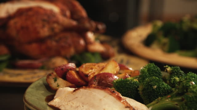 cu, selective focus, steaming dish on plate, person carving roasted chicken in background - roast dinner stock videos & royalty-free footage