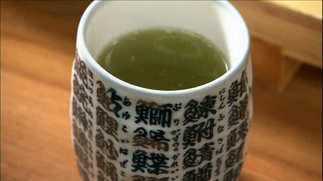 steaming green tea fills a cup decorated with chinese fish radicals. - chinese tea cup stock videos and b-roll footage