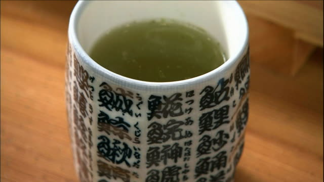 steaming green tea fills a traditional cup. - chinese tea cup stock videos and b-roll footage