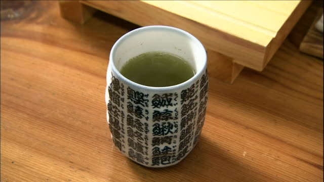 steaming green tea fills a traditional cup. - 温かいお茶点の映像素材/bロール