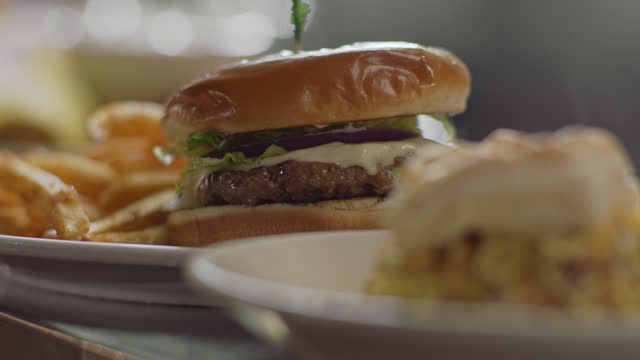 slo mo. cu. a steaming hot breakfast sandwich with fried potatoes are ready for pickup as a chef slides a plate with a cheeseburger and french fries on the counter in a diner - unhealthy eating stock videos & royalty-free footage