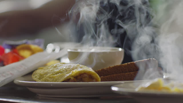 slo mo. cu. a steaming hot savory omelet with toast is ready for pickup on the counter in an authentic diner - toasted bread stock videos & royalty-free footage