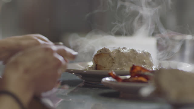 cu. a steaming hot savory plate of sausage gravy on a biscuit is ready for pickup on the counter in an authentic diner - buttermilk biscuit stock videos & royalty-free footage