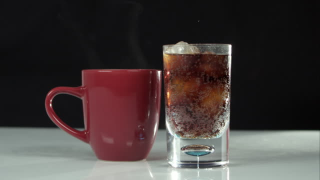 Steaming mug next to glass of soda.