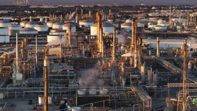 vídeos de stock e filmes b-roll de steaming oil refinery at sunset - aerial shot - wilmington cidade de los angeles