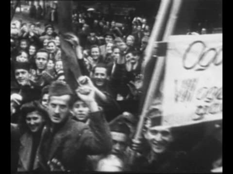 steampowered cart moves through belgrade street as crowds line street after liberation of belgrade / pan cheering yugoslavs in belgrade some hold... - 1944 stock-videos und b-roll-filmmaterial
