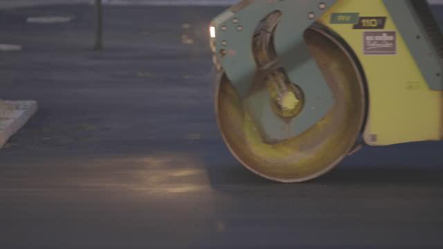vídeos de stock, filmes e b-roll de rolo compressor compactando asfalto na rua da cidade à noite - pista asfaltada