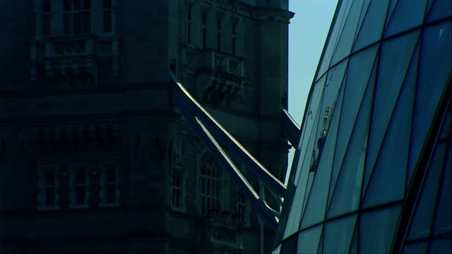 steel beams extending out from tower bridge appear to connect to london city hall. available in hd. - gla building stock videos & royalty-free footage
