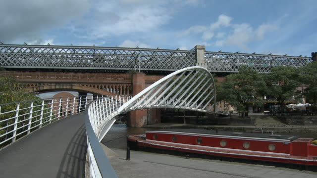 ms, steel foot bridge and railway bridges crossing bridgewater canal, castlefield, manchester, england - canal stock videos & royalty-free footage