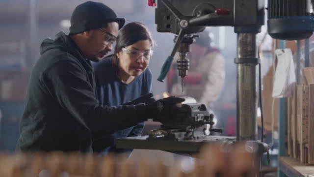 slo mo cu of steel hammers in foreground, warehouse manager and employee prepare to drill hole in hammer head in background - silver coloured stock videos & royalty-free footage