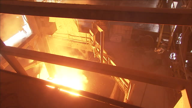 a steel mill cauldron emits billowing flames. - steel worker stock videos & royalty-free footage