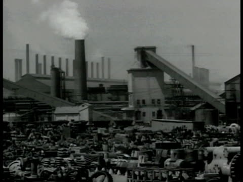 Steel mill factory w/ smoke stack INT WS Rows of large stone containers sparks from fire HA WS Mechanics in factory airplane incomplete single engine...