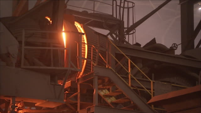 a steel mill furnace emits sparks and billowing flames. - stahl stock-videos und b-roll-filmmaterial