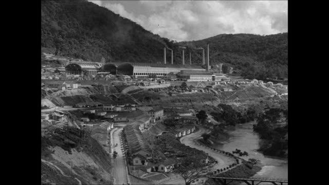 Steel mill HA WS Mill smoke stacks INT Brazilian foundry workers pouring molten steel MS Chainsaw cutting metal rail sparks flying Bessemer...