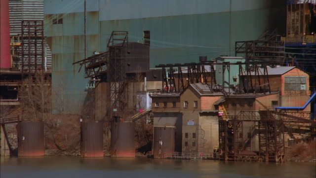 a steel mill occupies a long stretch of river. available in hd. - ドラム容器点の映像素材/bロール