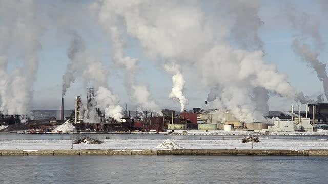 ls pan steel mills spewing smoke on a river / sault sainte marie, canada - mill stock videos & royalty-free footage