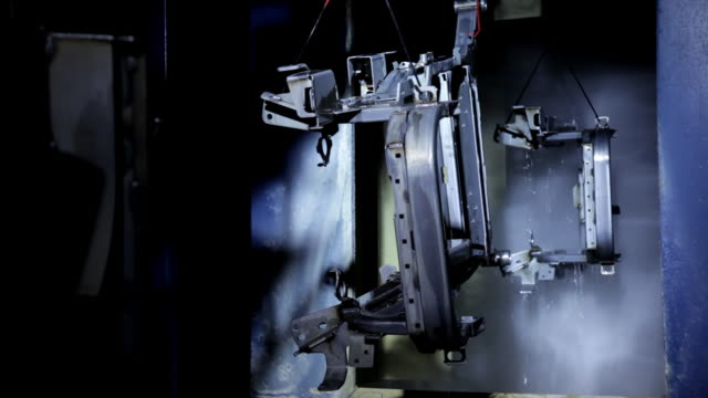 Steel parts are washed prior to painting and move along the assembly line in a US manufacturing factory.